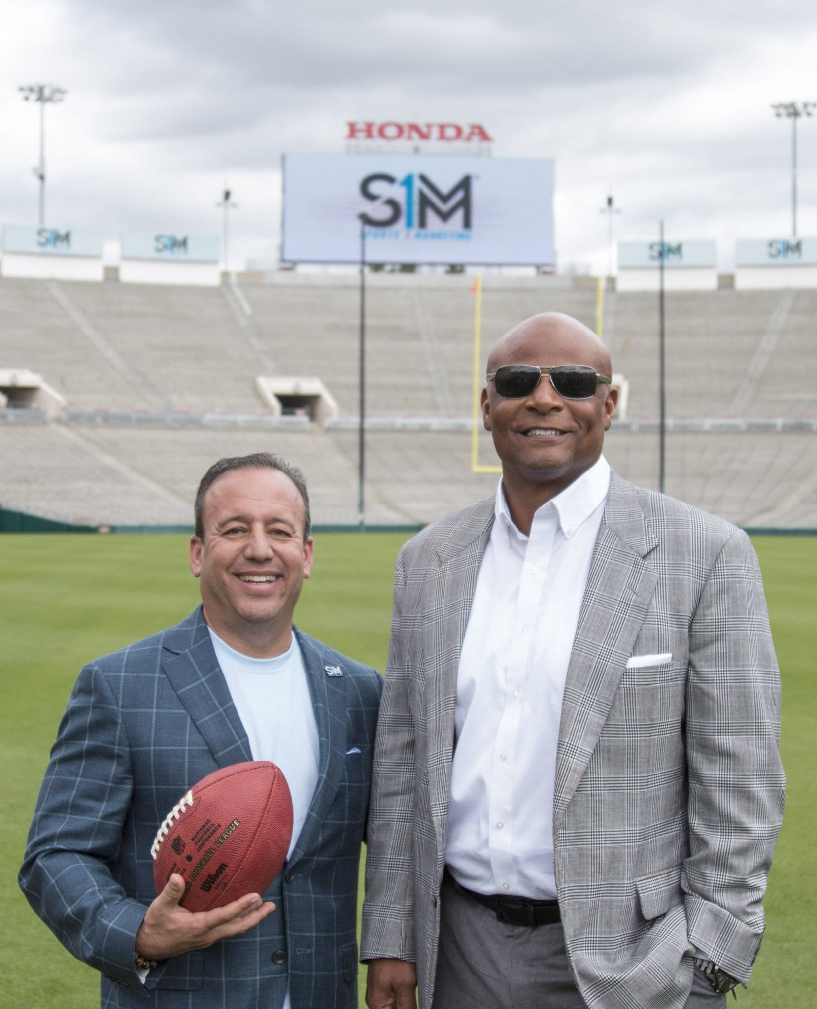 Two men in suits standing on a football field