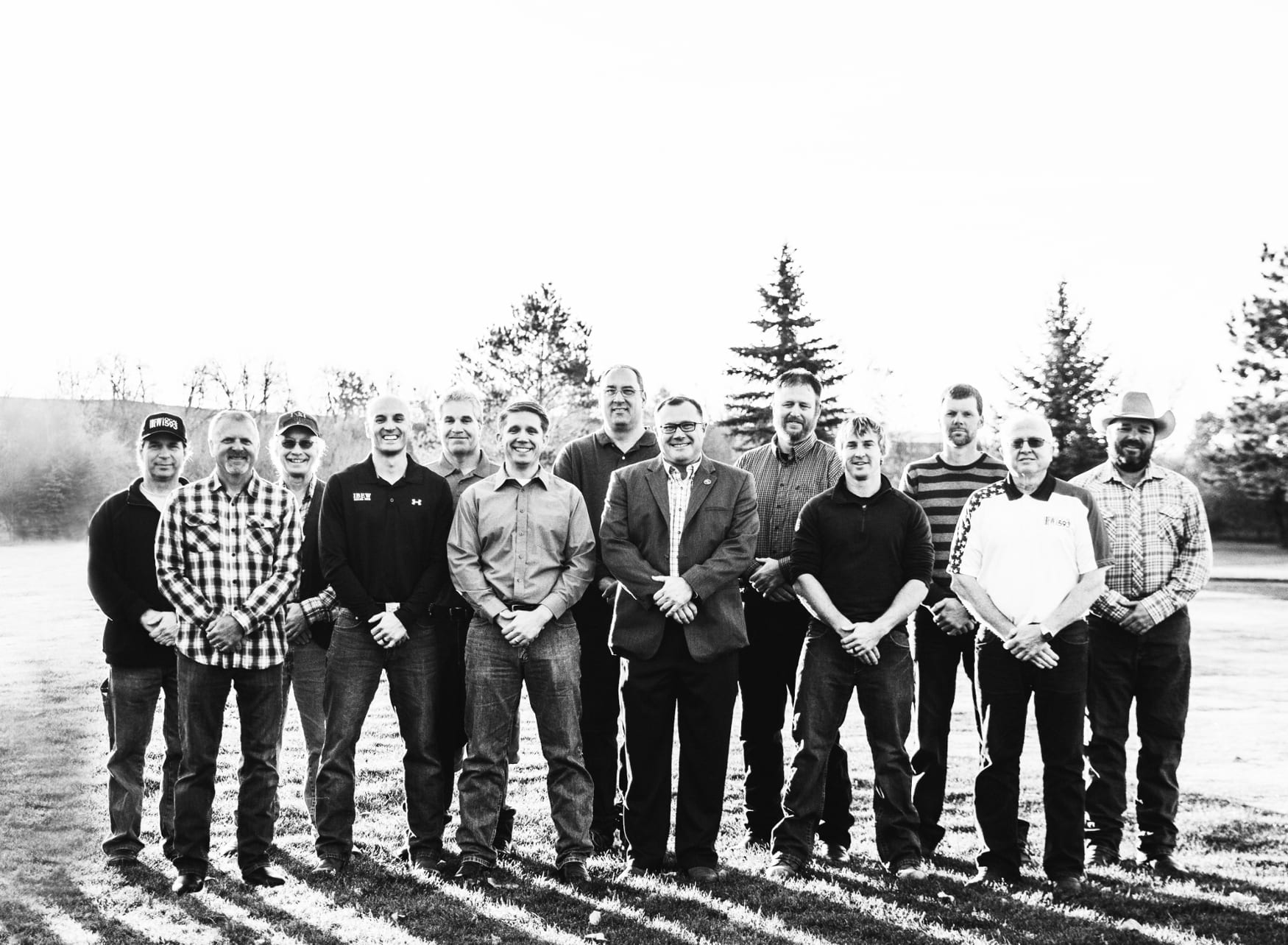 Black and white photo of 13 men wearing jeans and standing in a yard